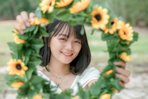 Young cheerful ethnic female demonstrating colorful sunflower wreath while looking at camera in park
