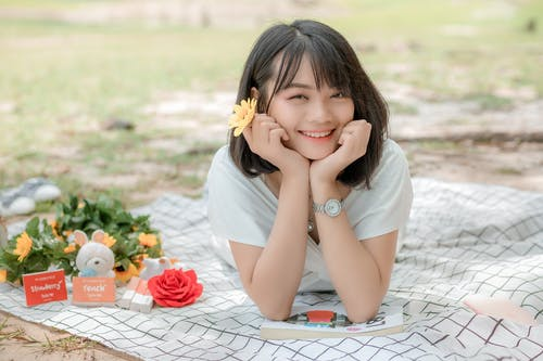Smiling Asian female relaxing on blanket with flowers and book while leaning on hands and enjoying summer day in park