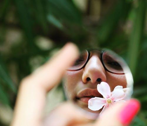 Woman in Black Framed Eyeglasses Holding White Flower