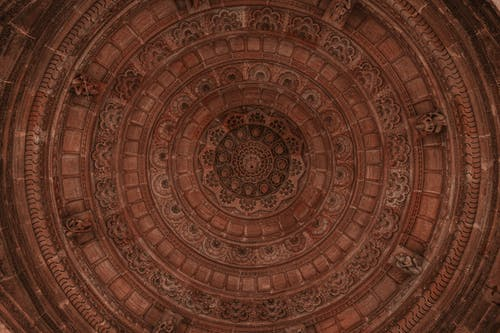 From below of aged stone circle shaped ceiling with geometric decor and small statues in temple