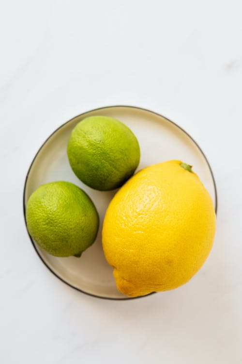 Top view of big whole lemon and limes placed on metal plate on white surface