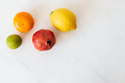 From above of various colors ripe lime and tangerine and pomegranate and lemon placed on white table