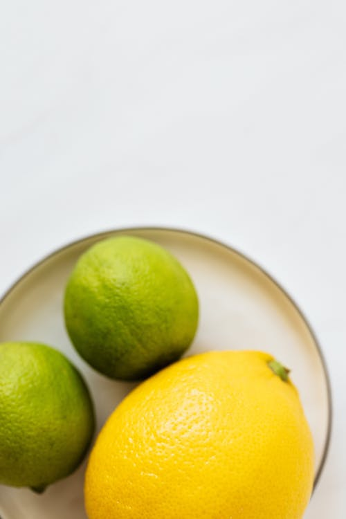 Top view of closeup whole ripe big lemon and limes served on white metal plate on white surface