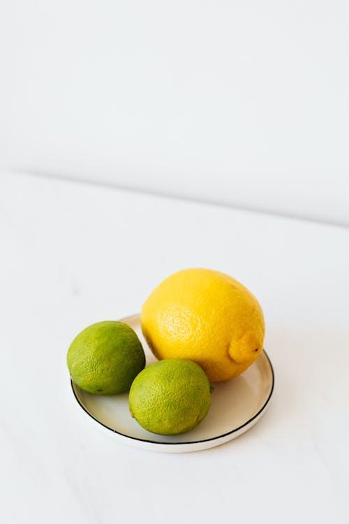 Lemon and limes on metal plate