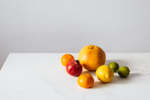 Citrus fruits and pomegranate placed on white table