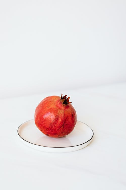 Ripe pomegranate on metal plate on white table
