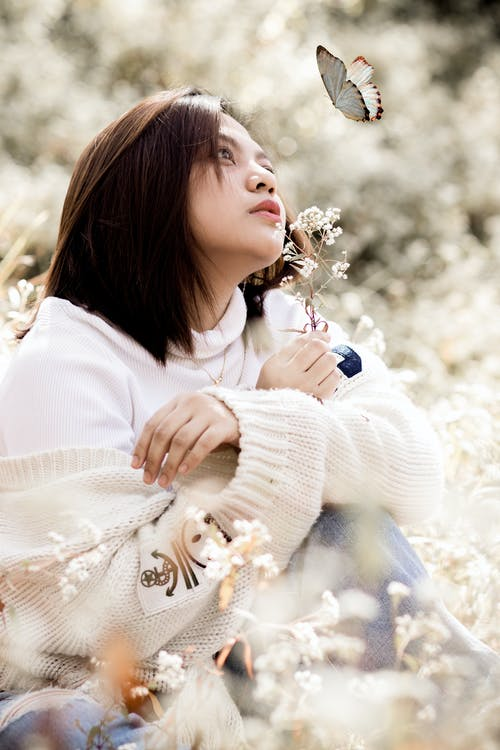 Woman in White Sweater Holding White Flowers