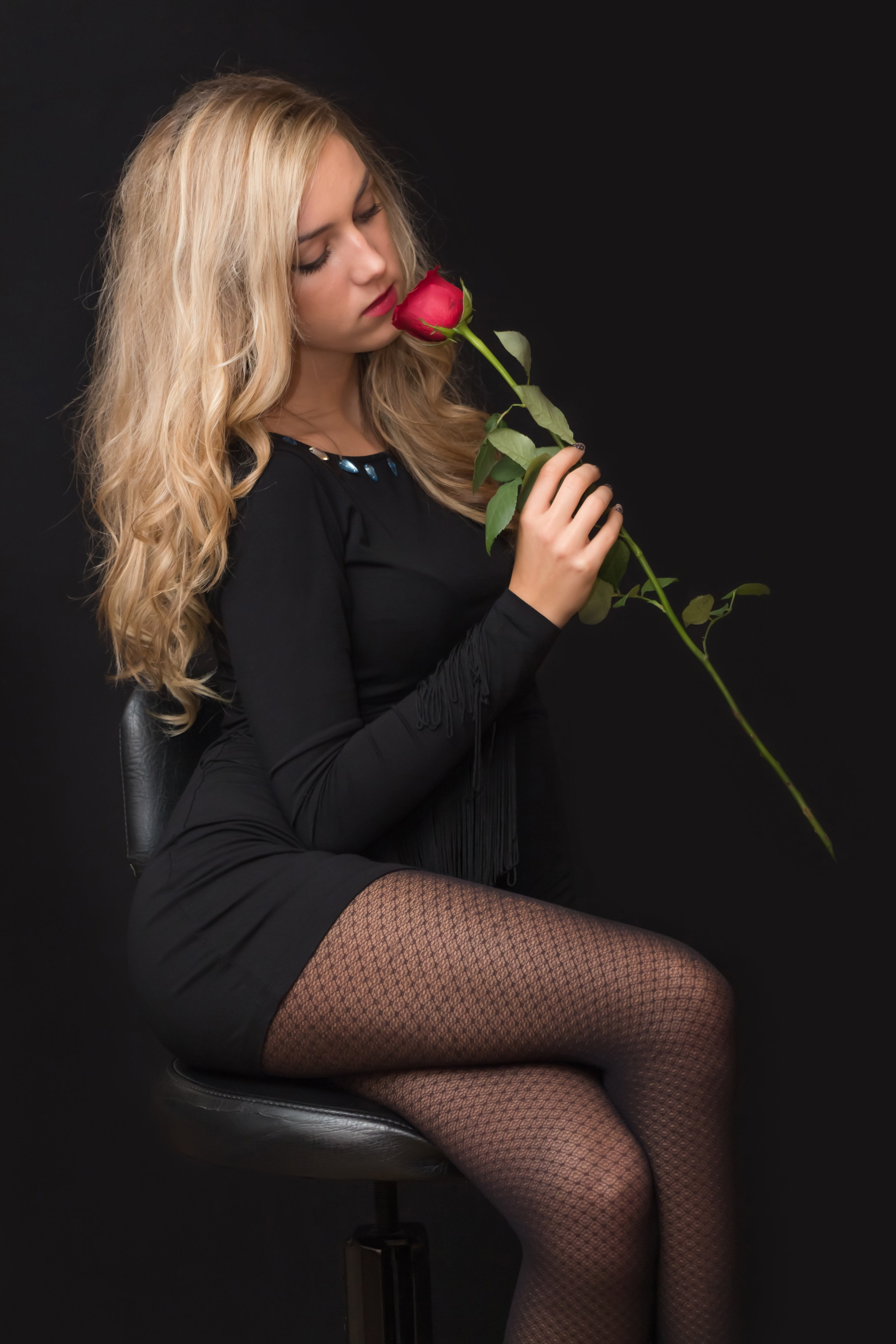 Woman in Black Dress Holding Red Rose