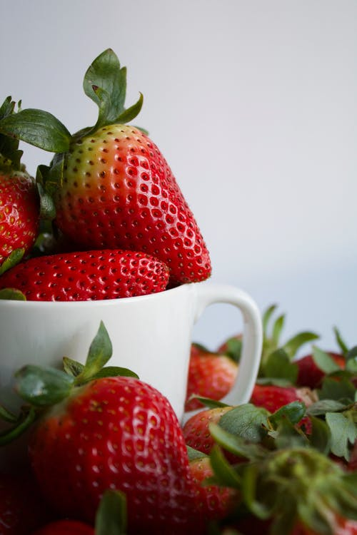 Heap of ripe fresh strawberries in cup on white background