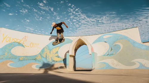 Man in Black Shirt and Black Pants Riding Skateboard