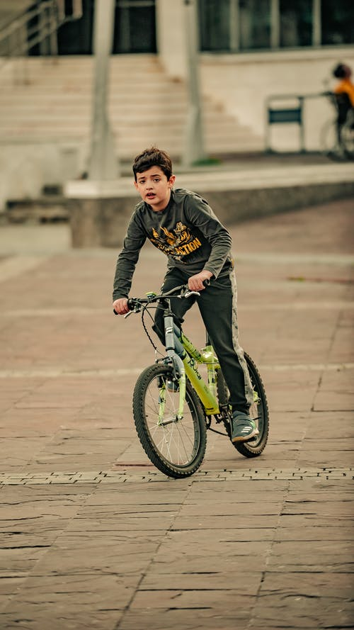 Ethnic boy driving bicycle on pavement behind stairs in city