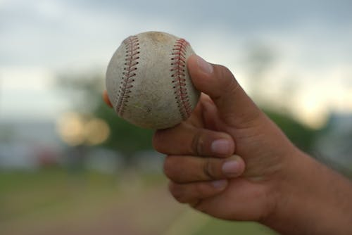 White and Red Baseball on Persons Hand
