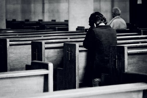 Black and white back view of anonymous male believers standing on knees near wooden benches with symbol of cross on surface during mass in cathedral