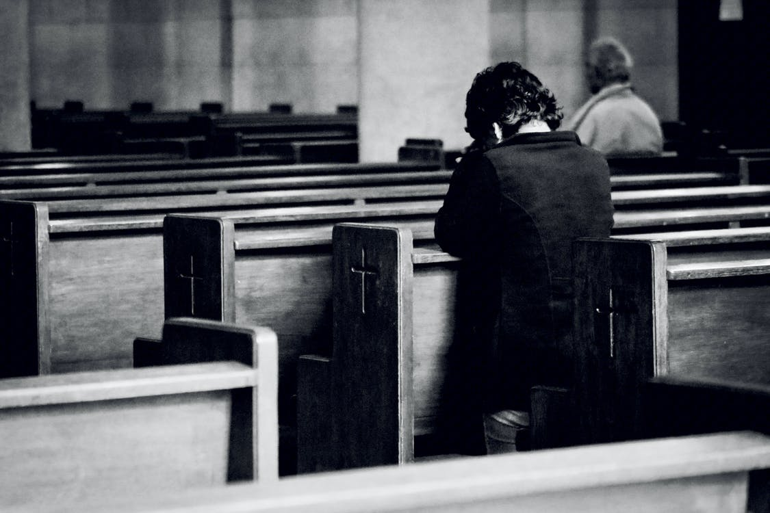 Unrecognizable men praying in old catholic church