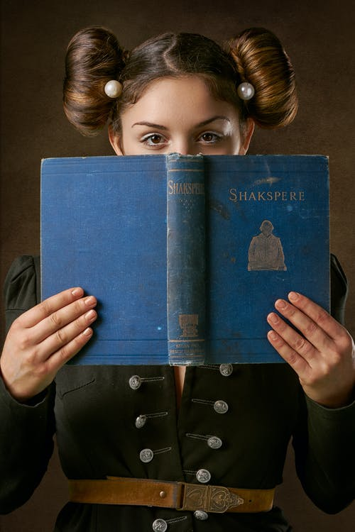 Girl Holding Blue Book With Girl in Black Coat