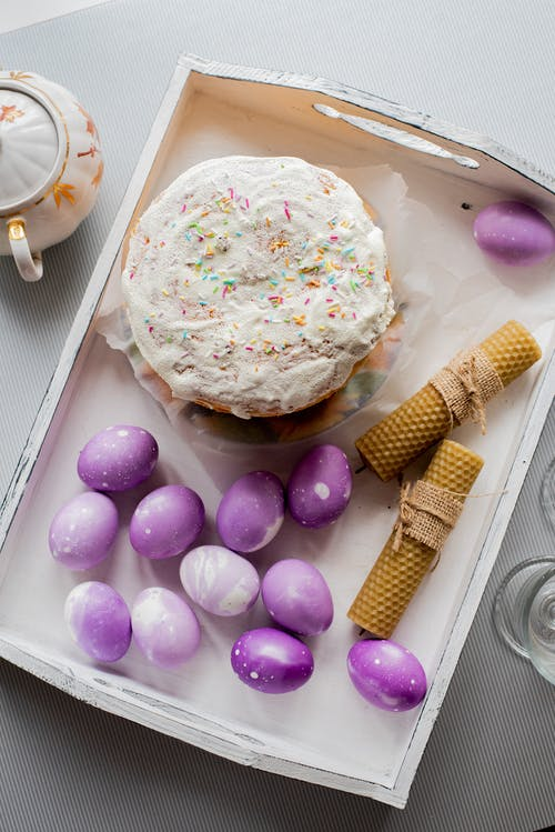 Easter cake and purple eggs on white tray