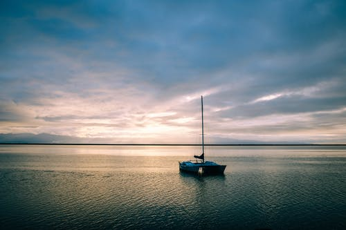 Boat floating in calm rippling sea water running under evening sky full of clouds in summer day