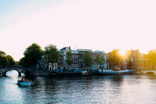 Scenery of aged houses on river bank during sunset