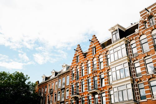 Low angle exterior of contemporary narrow apartment buildings of brown color with white decorative elements in Dutch style