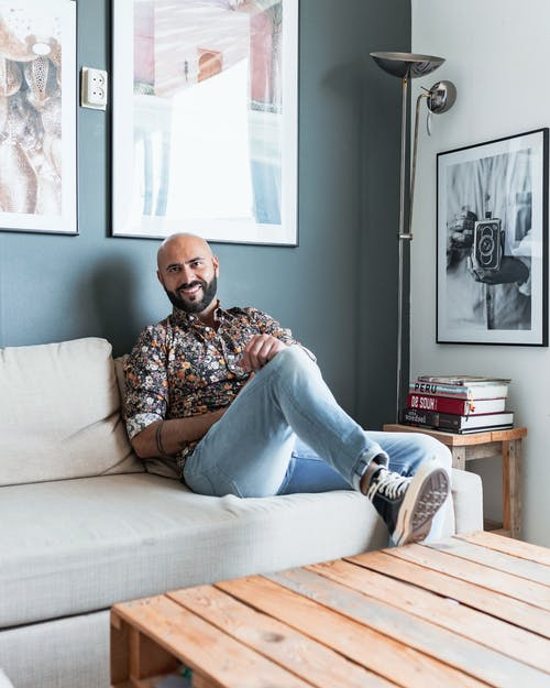 Man in Brown and White Floral Shirt and Blue Denim Jeans Sitting on White Couch