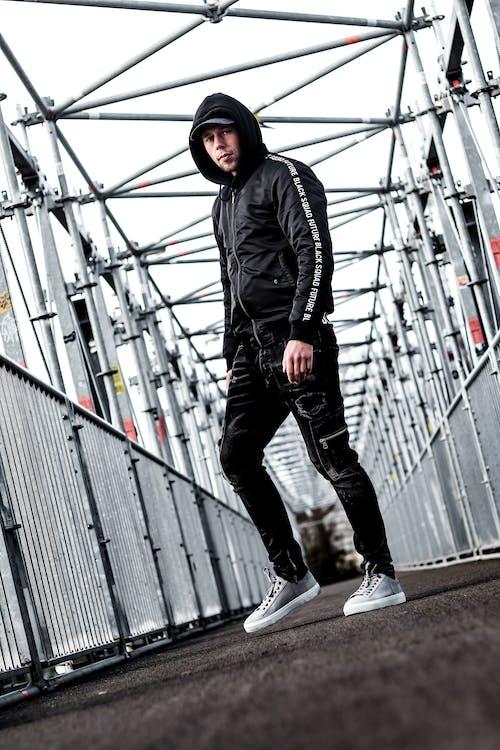 Man in Black Leather Jacket and Black Pants Standing on Gray Metal Bridge