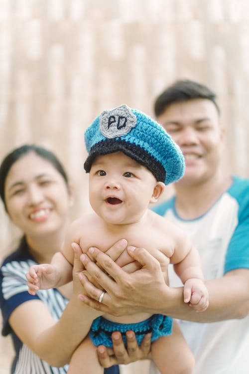 Selective Focus Photo of a Cute Baby being Carried by His Parents