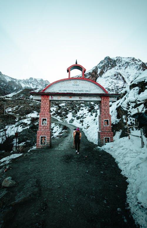 Unrecognizable woman walking through brick gate in mountainous terrain