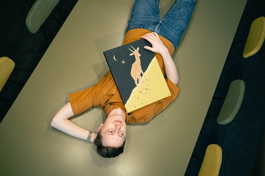 Man With a Painting Laying Down on a Table