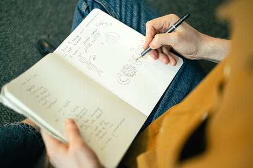 Person Holding Pen and Writing on a Notebook