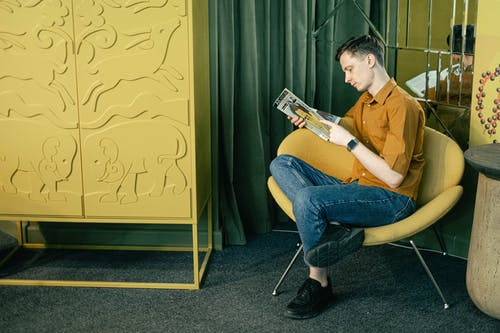 Man Sitting on a Chair and Reading a Magazine
