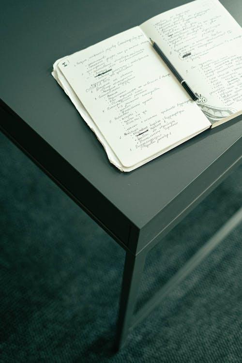 Kostnadsfri bild av anteckning, anteckningar, anteckningsbok, bord