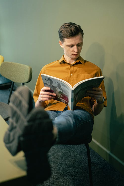 Man with Legs Crossed Reading Book