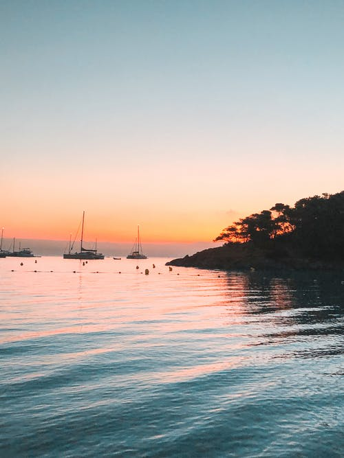 Sailboats floating on calm seawater during sunset
