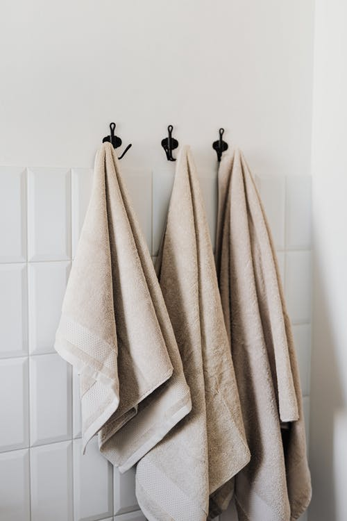 Beige hand towel and face towel and floor towel hooked in bathroom against white tiles in hotel room