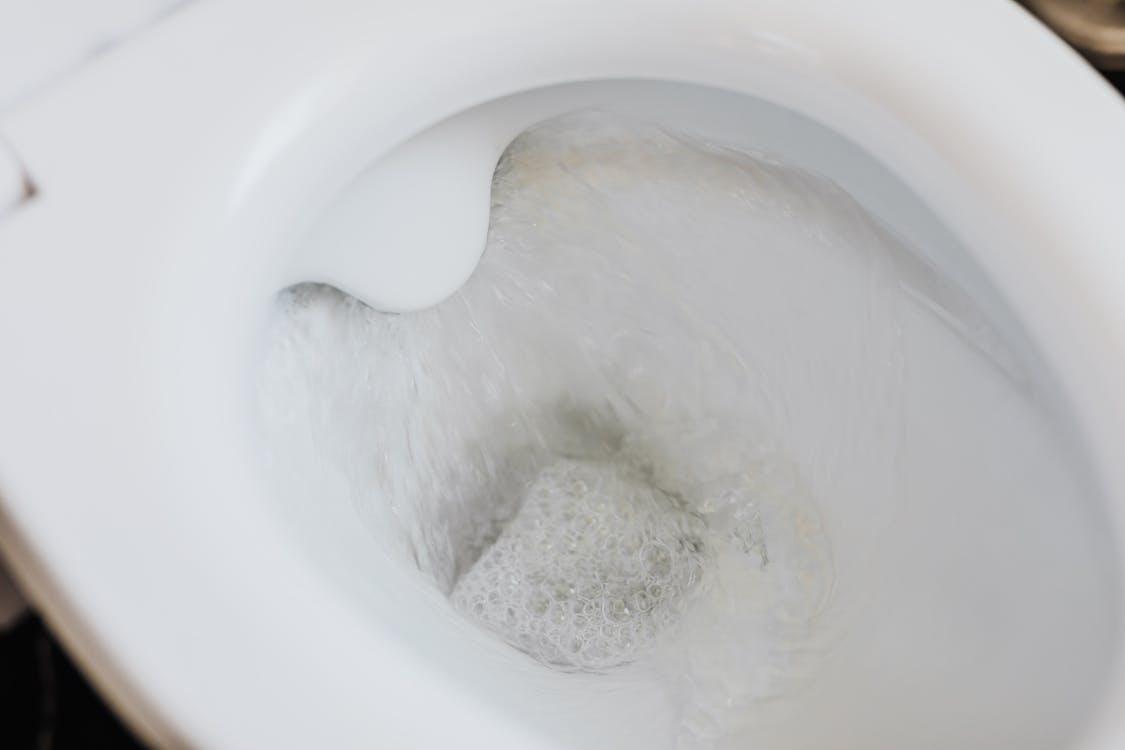 Flushing water in white toilet bowl