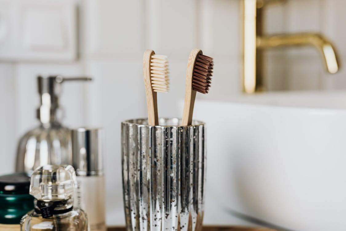 Eco friendly bamboo toothbrushes in silver glass placed in bathroom near sink and beauty products