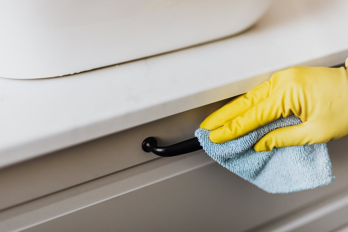 From above of crop faceless person in yellow gloves cleaning handle of cabinet with microfiber cloth in modern bright bathroom