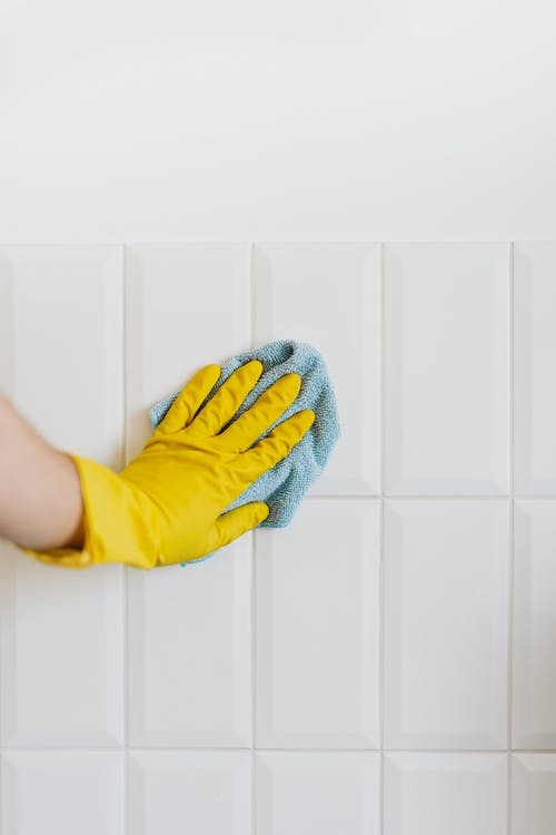 Crop person cleaning white tile wall with microfiber cloth