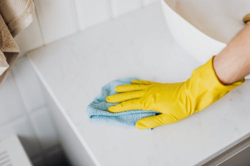 From above crop unrecognizable person with microfiber cloth wearing yellow rubber glove and cleaning white marble tabletop of vanity table with washbasin in bathroom