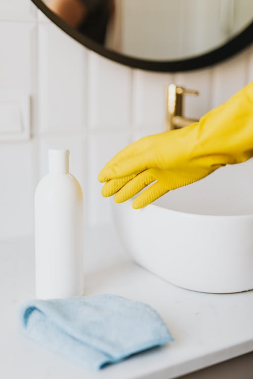 Crop person in cleaning glove in bathroom