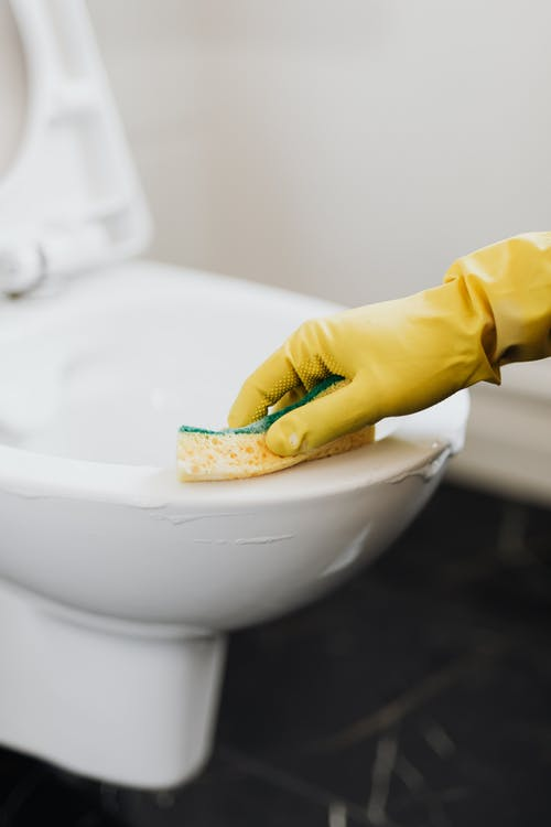 Crop anonymous person wearing yellow cleaning glove removing stains on toilet bowl with sponge in washroom