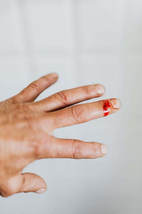 Crop unrecognizable male back hand bleeding from cut finger wound against white blurred wall