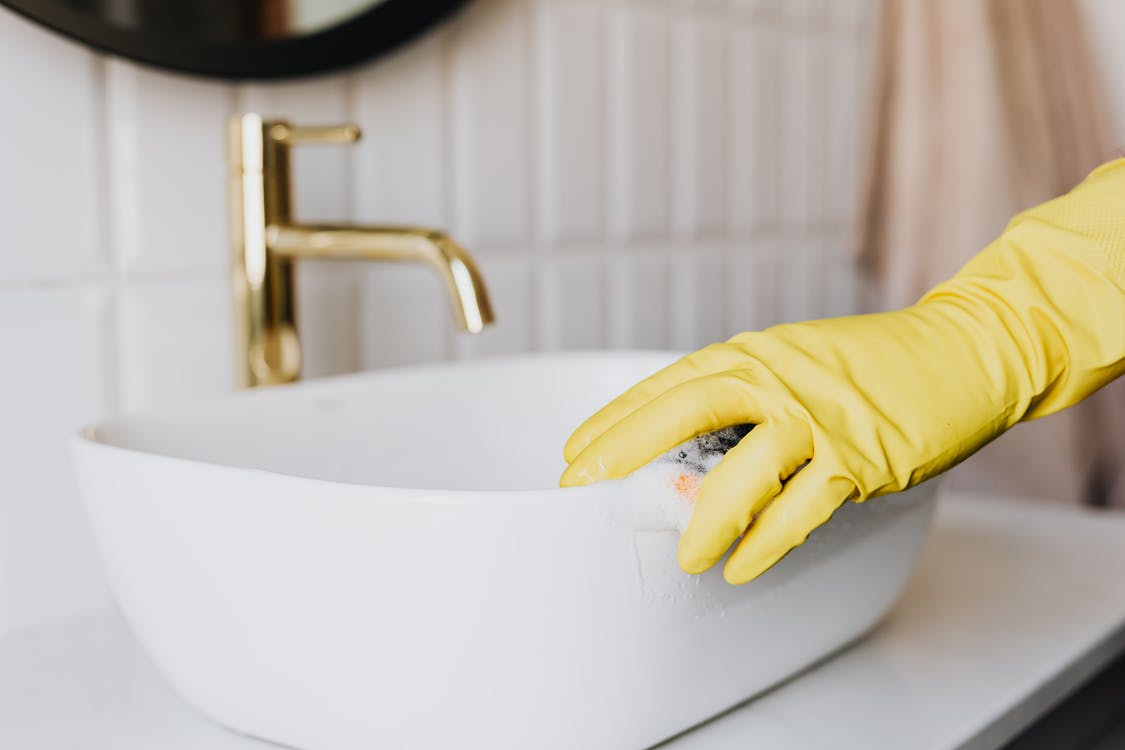 Person in glove cleaning bathroom sink