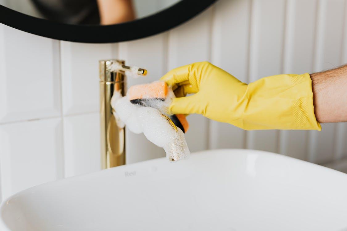 Crop man washing faucet in bathroom