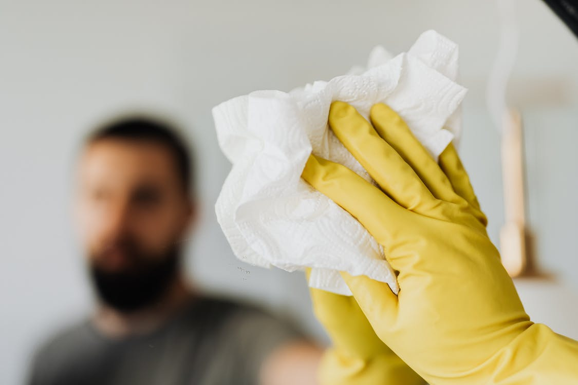 Unrecognizable bearded male wearing yellow latex gloves wiping mirror with napkin in bathroom at home