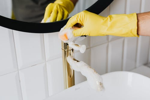 Anonymous person wearing yellow latex gloves washing golden faucet with sponge in modern bathroom while cleaning house