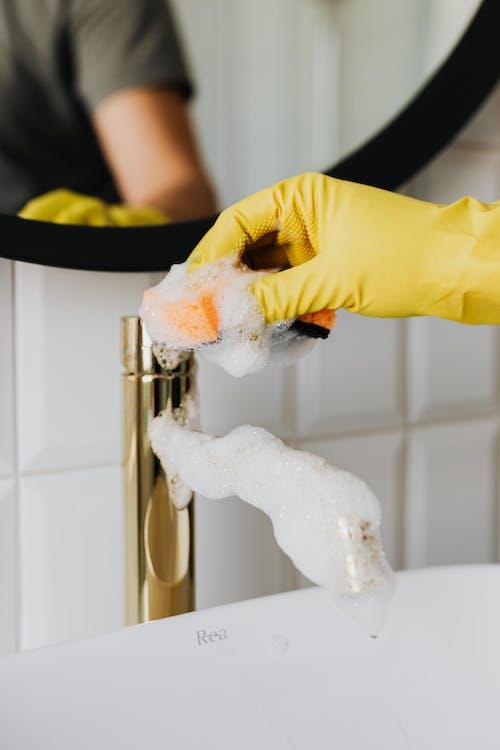 Unrecognizable person washing golden faucet with sponge