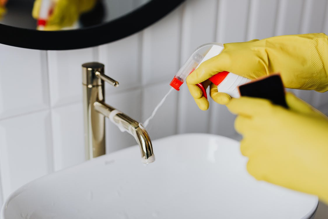 Faceless cleaner in gloves tiding up bathroom