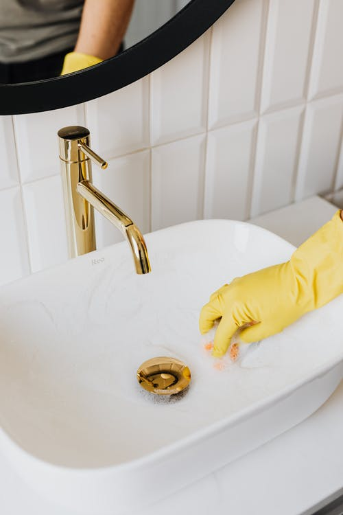 Faceless man cleaning sink in bathroom
