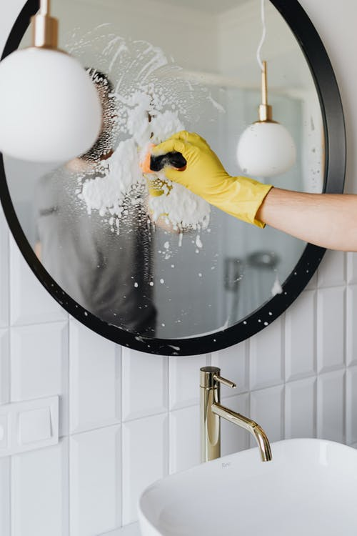 Faceless person cleaning mirror in bathroom